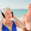 Woman listening to some music at the beach — Stock Photo #10853156