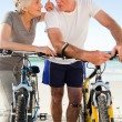 Retired couple with their bikes on the beach — Stock Photo #10853295