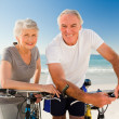 Retired couple with their bikes on the beach — Stock Photo #10853304