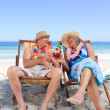 Mature couple sitting on deck chairs — Stock Photo #10853825