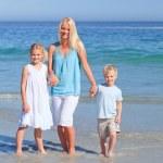 Joyful family walking on the beach — Stock Photo #10854172