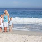 Joyful family walking on the beach — Stock Photo #10854254