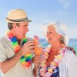 Elderly couple drinking a cocktail on the beach — Stock Photo #10854480