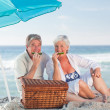 Elderly couple picniking on the beach — Stock Photo