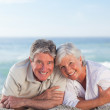 Mature couple lying down on the beach — Stock Photo #10854667