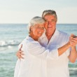 Mature couple dancing on the beach — Stock Photo