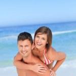 Handsome man having wife a piggyback on the beach — Stock Photo #10855113
