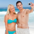 Couple taking a photo of themselves on the beach — Stock Photo