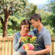 Man offering flowers to his girlfriend — Stock Photo #10856532