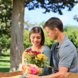 Man offering flowers to his girlfriend — Stock Photo