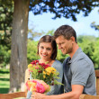 Man offering flowers to his girlfriend — Stock Photo #10856538