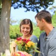 Young man offering flowers to his girlfriend — Stock Photo #10856543