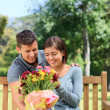 Young man offering flowers to his girlfriend — Stock Photo