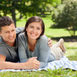 Couple lying down in the park — Stock Photo