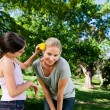 Mother and her daughter with a flower — Stockfoto