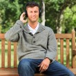Young man listening to some music on the bench — Stock Photo #10857068
