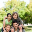 Parents giving children piggyback — Stock Photo #10857088