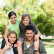 Parents giving children a piggyback - Stock Photo