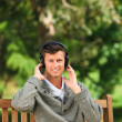 Young man listening to some music on the bench — Stock Photo