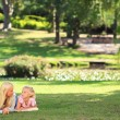 Mother with her daughter lying down in the park — Stock Photo