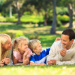 Stock Photo: Family lying down in park