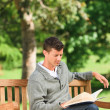 Young man reading his book on the bench — Stock Photo