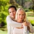 Woman hugging her boyfriend in the park — Stock Photo