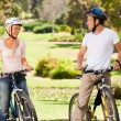 Couple with their bikes in the park - Stock Photo