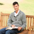Man reading his book on the bench — Stock Photo