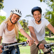 Couple in the park with their bikes - Stock Photo