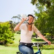 Woman in the park with her bike - Stock Photo