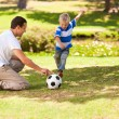 Foto Stock: Father playing football with his son