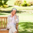 Senior woman listening to some music - Stock Photo