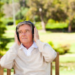 Retired man listening to some music - Stock Photo