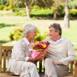 Senior man offering flowers to his wife — Stock Photo