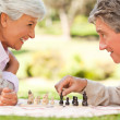 Elderly couple playing chess - Stock Photo
