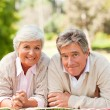 Mature couple lying down in the park — Stock Photo