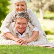 Mature couple lying down in the park - Stock Photo