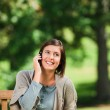Beautiful woman phoning on the bench — Stock Photo #10858380