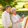 Retired couple painting in the park — Stock Photo #10858525