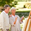Senior couple painting in the park — Stock Photo #10858527