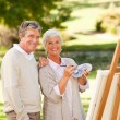 Senior couple painting in the park — Stockfoto