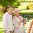 Senior couple painting in the park - Stock Photo