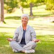 Mature woman practicing yoga in the park — Stock Photo