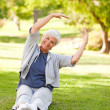 Stock Photo: Senior womdoing her stretches in park