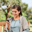 Young woman phoning on the bench — Stock Photo #10858698