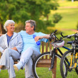 Elderly couple with their bikes - Stock Photo