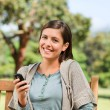 Young woman phoning on the bench — Stock Photo #10858732