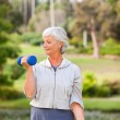 Mature woman doing her exercises in the park — Stock Photo #10858785