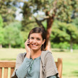 Young woman phoning on the bench — Stock Photo #10858793